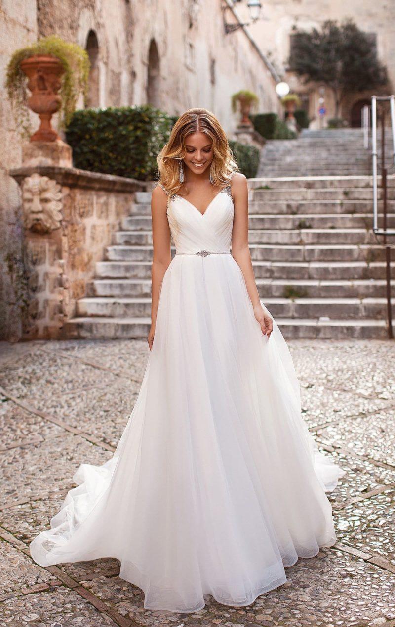 Свадебное платье с сияющими бретелями и многослойной юбкой.