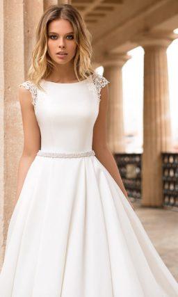Атласное свадебное платье с кружевным рукавом и открытой спинкой.