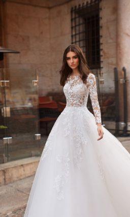 Романтичное свадебное платье с многослойным низом и длинным рукавом.