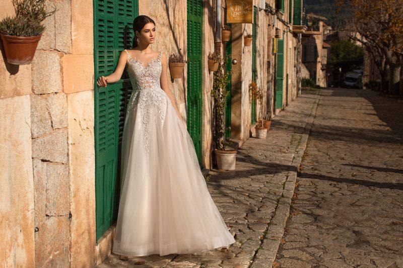 Свадебное платье с облегающим верхом и многослойной юбкой.