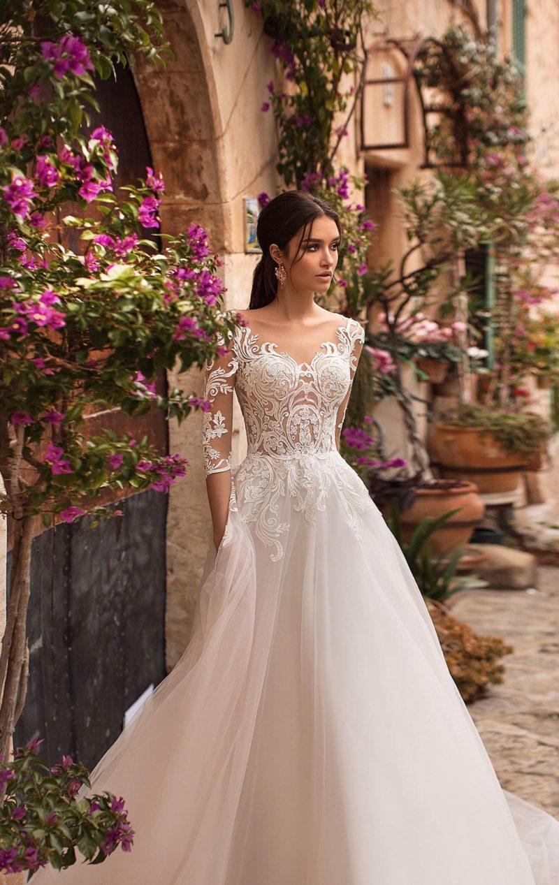 Романтичное свадебное платье с пышным шлейфом и рукавом до локтя.