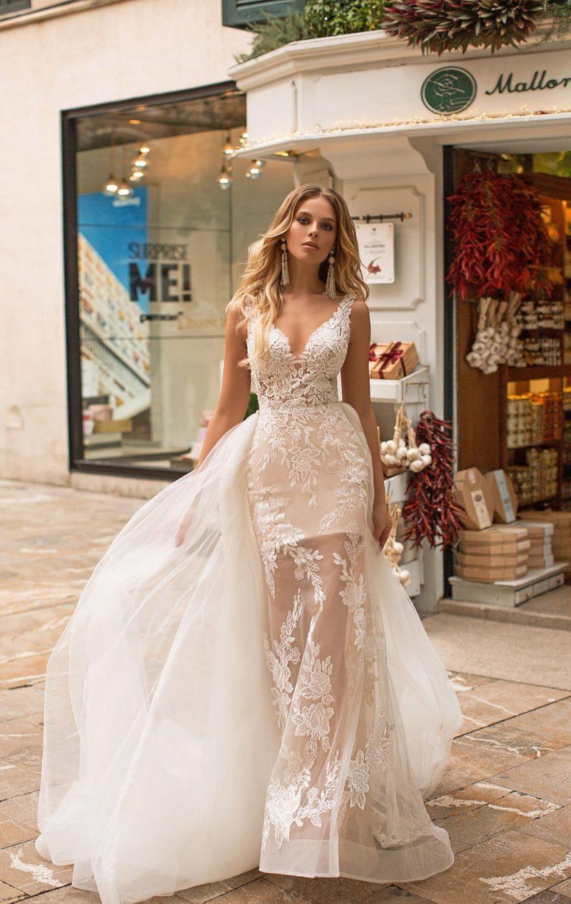 Свадебное платье кремового цвета с пышным шлейфом и V-образным вырезом.