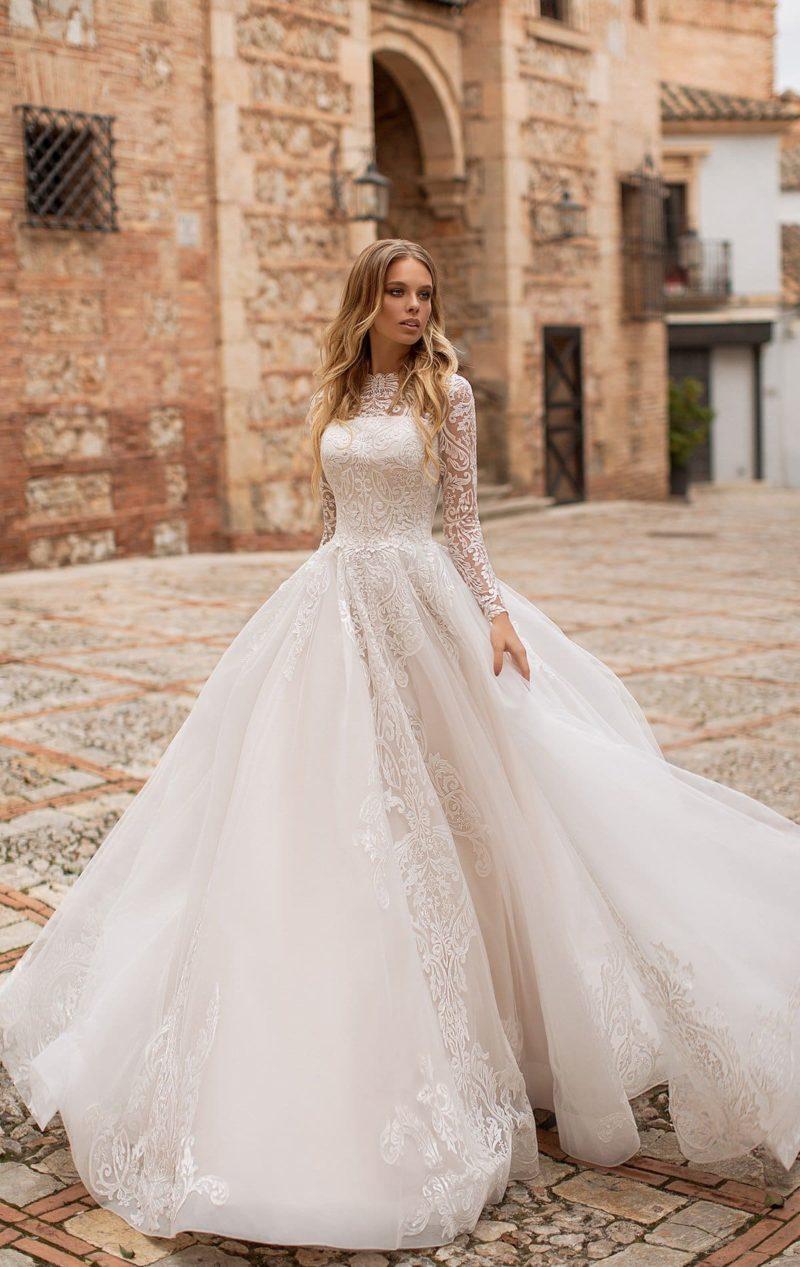 Закрытое свадебное платье с кружевным декором и пышной юбкой.