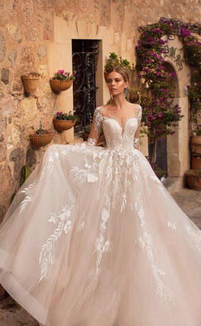 Воздушное свадебное платье с прозрачным рукавом и кружевным декором.