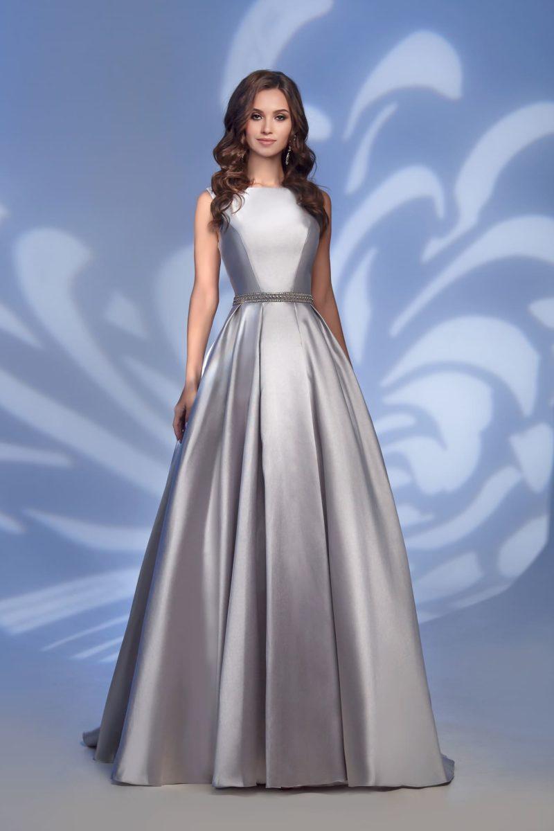 Серебристое вечернее платье с юбкой в пол и поясом из стразов.