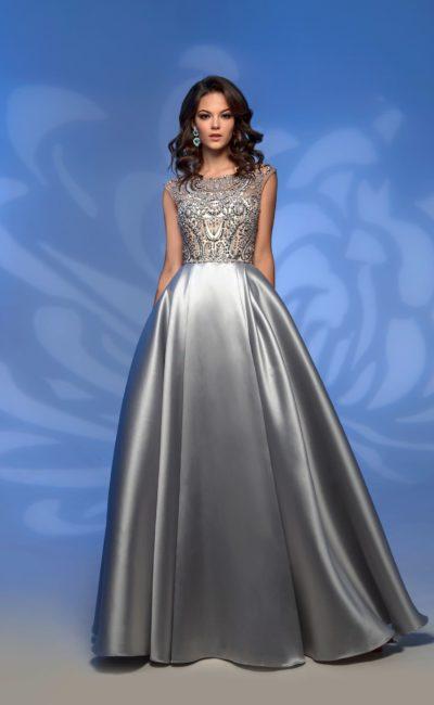 Серебристое вечернее платье с объемным низом и сияющим верхом.