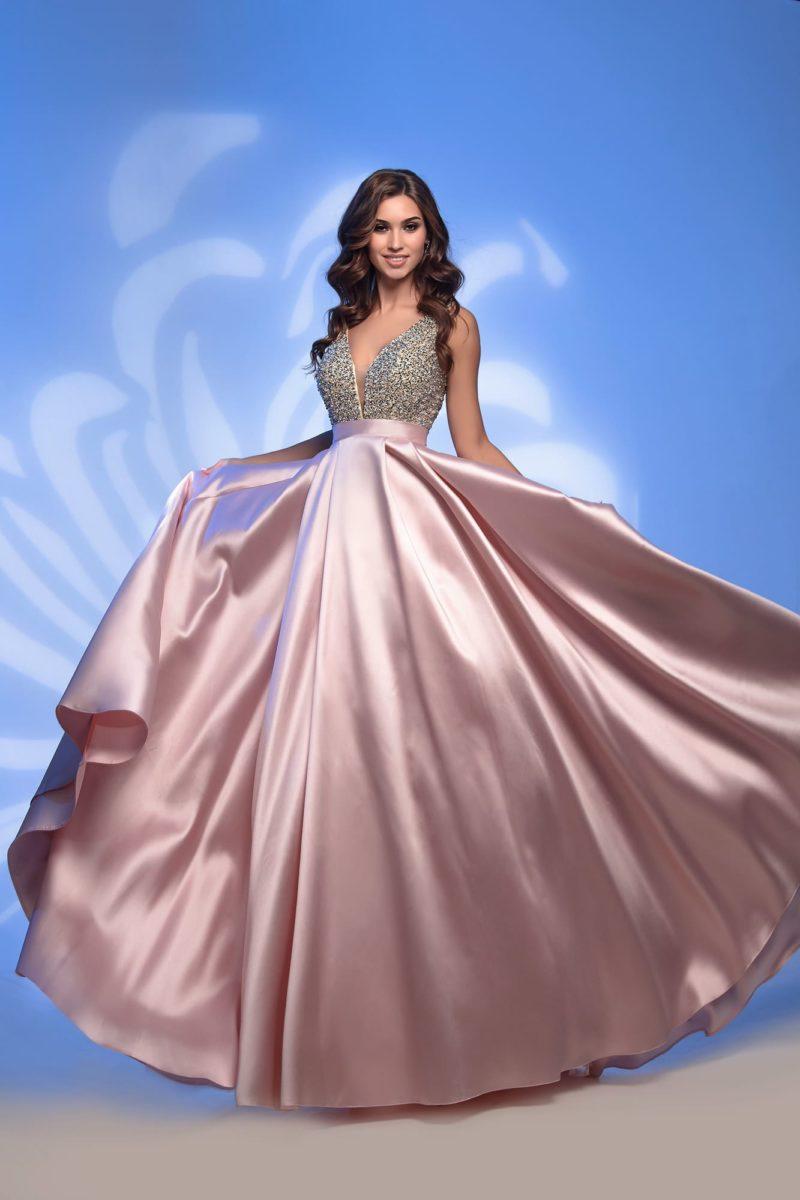 Розовое вечернее платье с юбкой в пол и глубоким вырезом.