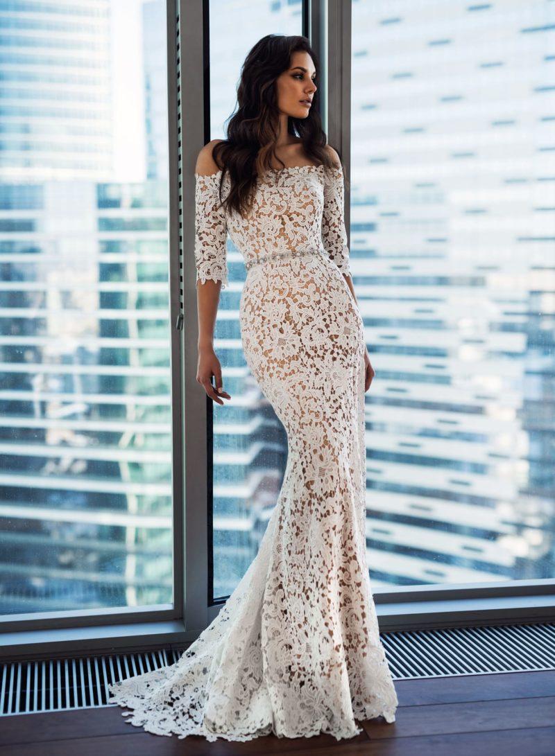 Облегающее свадебное платье с портретным декольте и узким поясом.