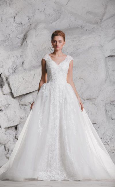 Свадебное платье с кружевным декором и пышным шлейфом.