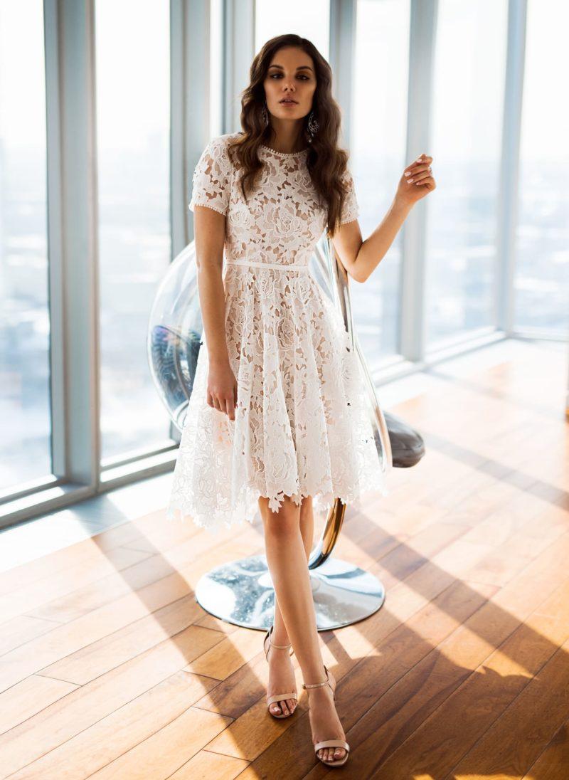 Бежевое свадебное платье с коротким рукавом и узким поясом.