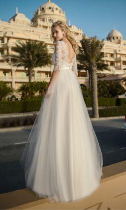 Пышное свадебное платье с кружевным рукавом и широким поясом.
