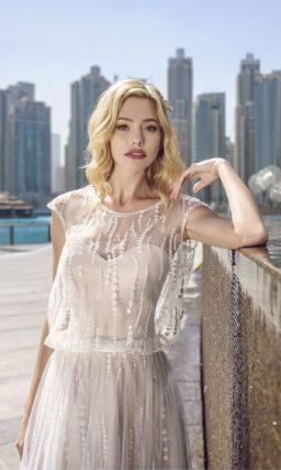 Пышное свадебное платье с полупрозрачным верхом и открытой спиной.