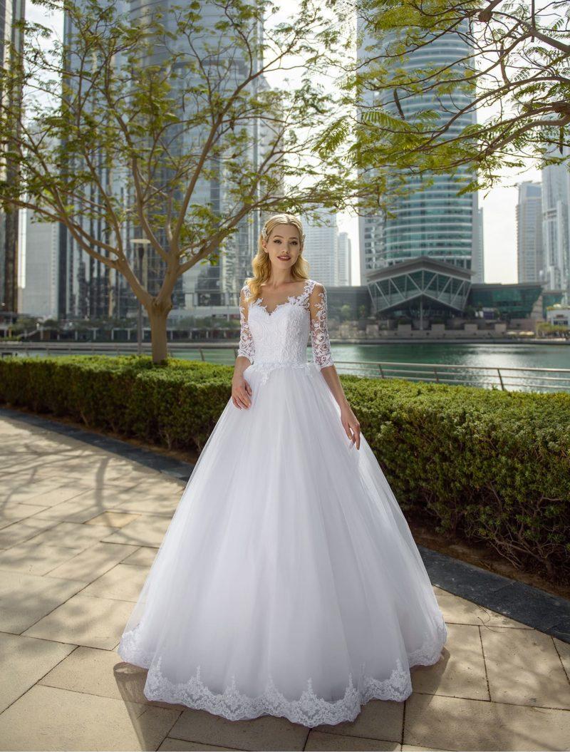Пышное свадебное платье с рукавом три четверти и кружевом по подолу.