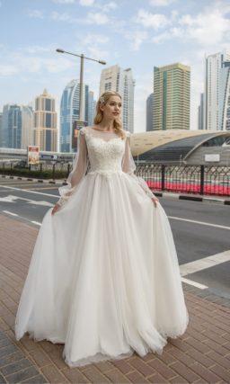 Пышное свадебное платье с длинным полупрозрачным рукавом с манжетами.