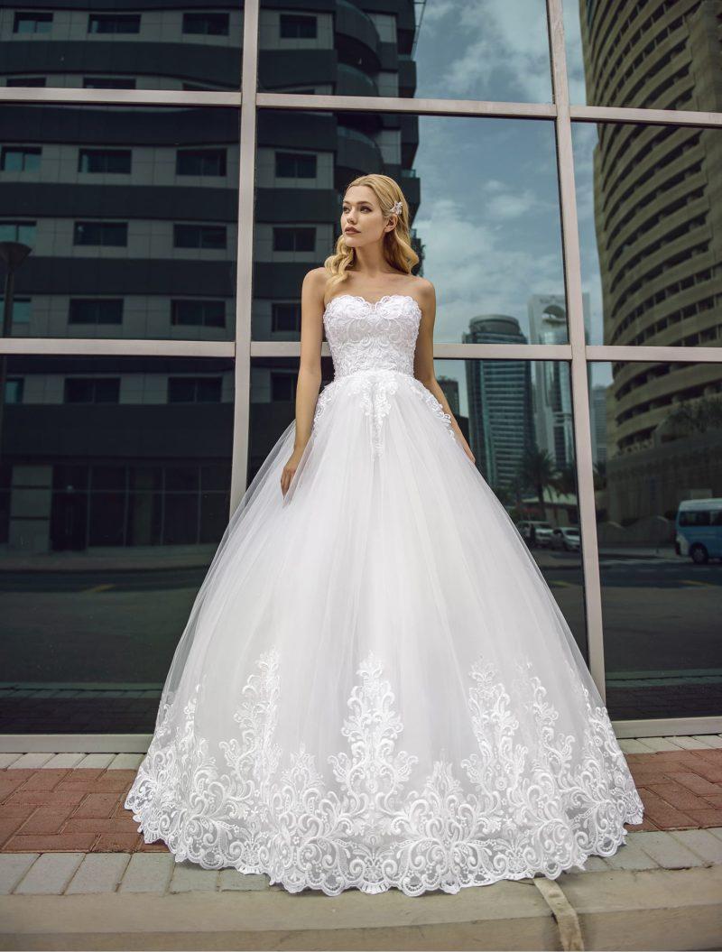 Открытое свадебное платье пышного силуэта с кружевом по подолу.