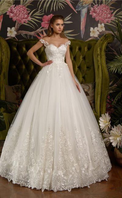 Свадебное платье пышного кроя, декорированное глянцевым кружевом.