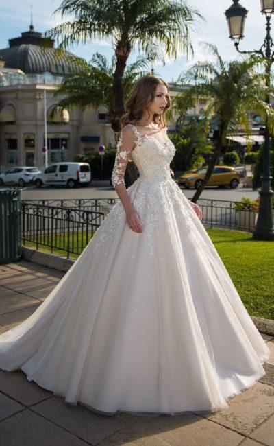 Свадебное платье пышного кроя с объемной отделкой и рукавом.