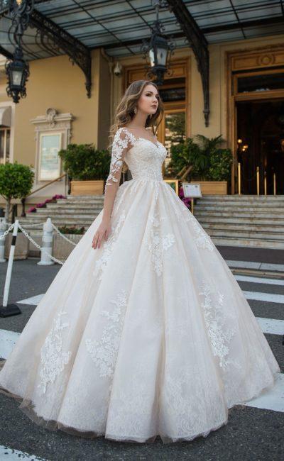 Пышное свадебное платье с прозрачным рукавом и декором из кружева.
