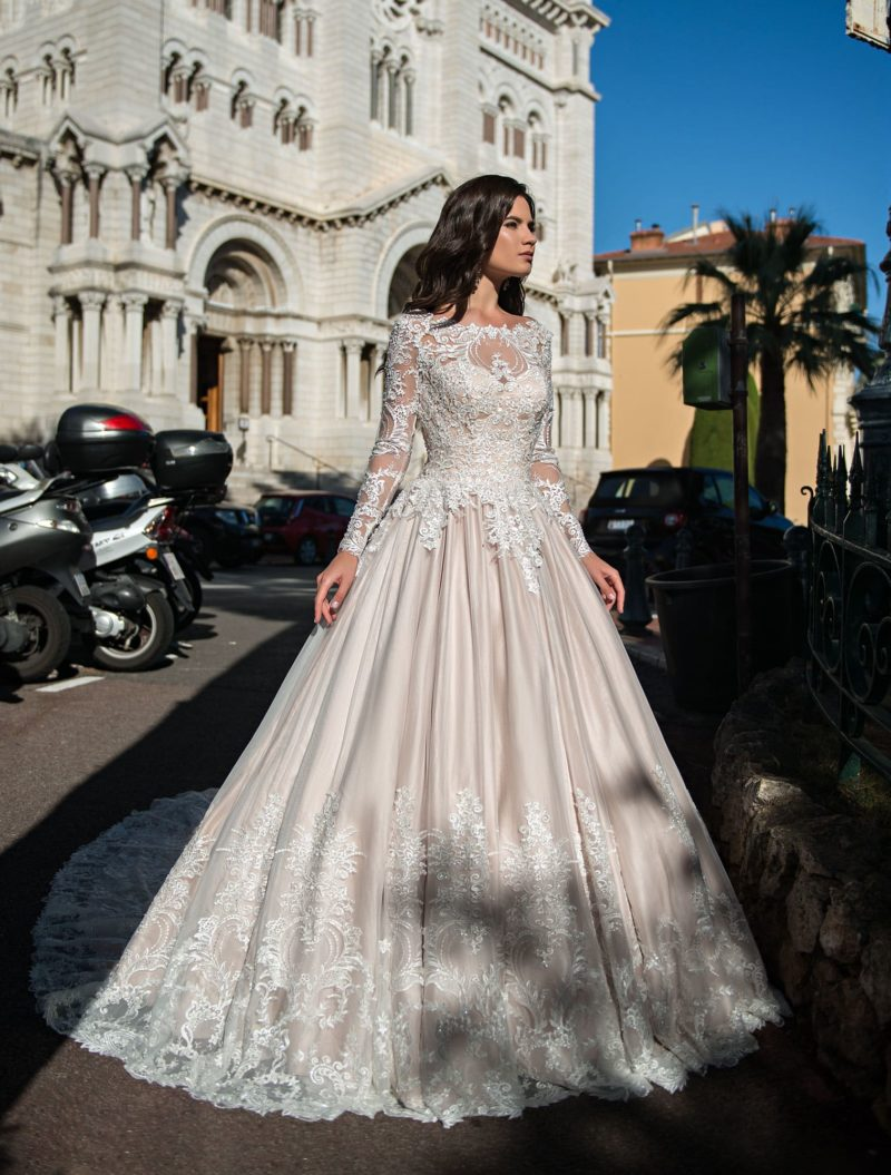 Свадебное платье оттенка слоновой кости с роскошным кружевным рукавом.
