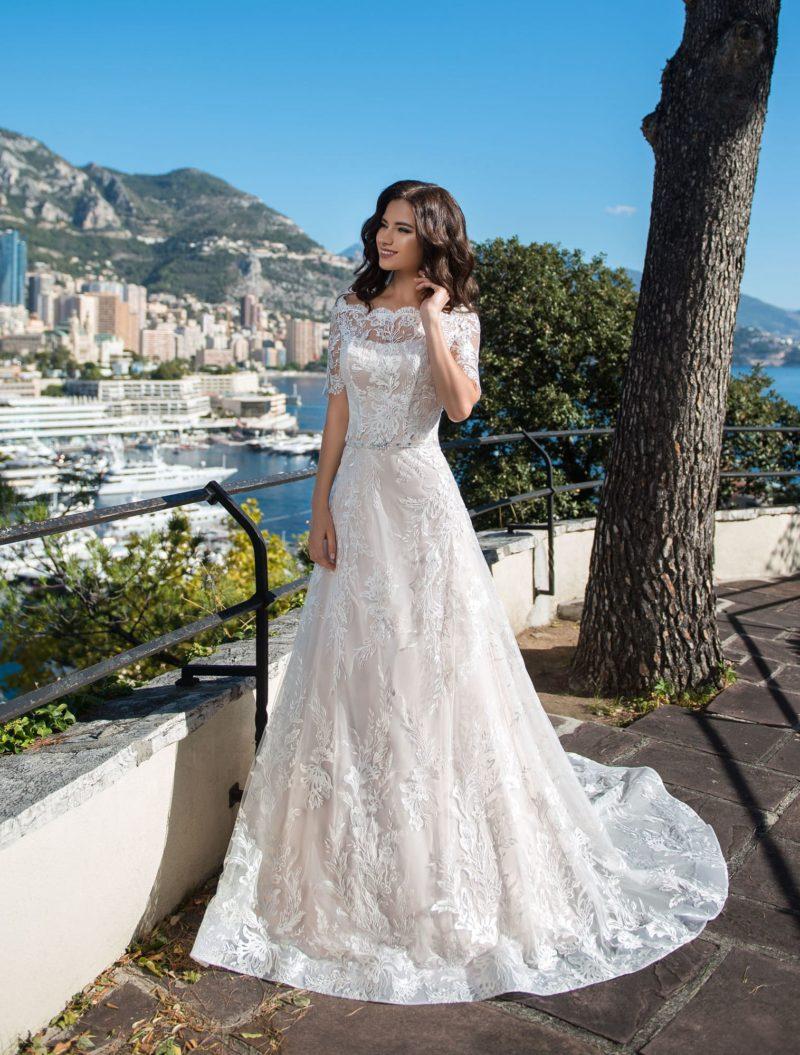 Свадебное платье с длинным шлейфом и блестящим поясом.