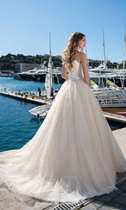 Пышное свадебное платье с открытым лифом и отделкой складками по юбке.