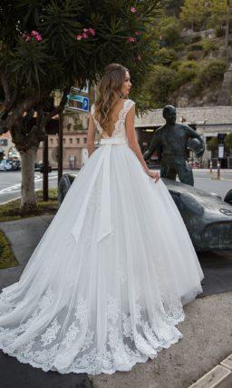 Пышное свадебное платье с открытой спинкой и бантом на поясе.