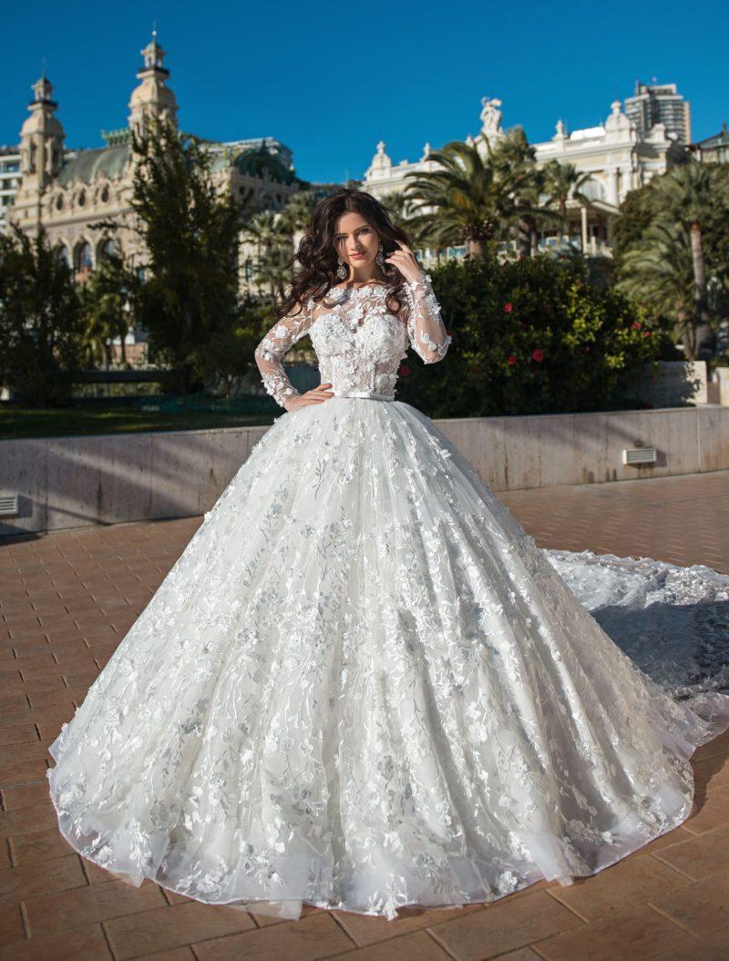 Пышное свадебное платье с узким поясом и объемным декором.