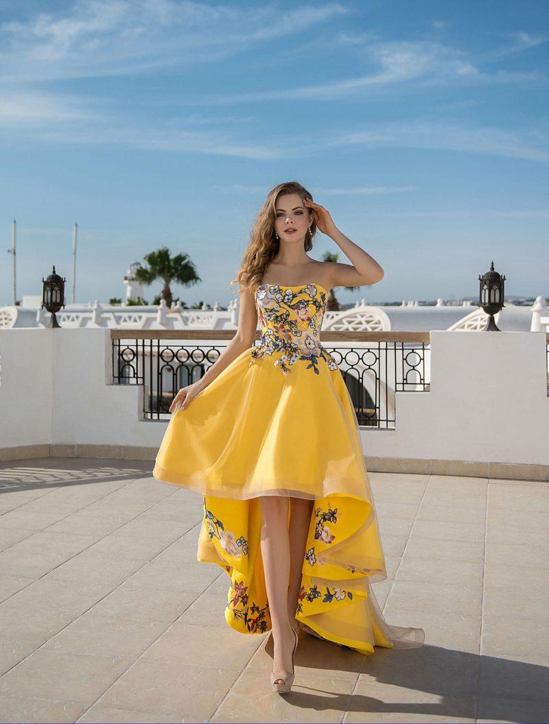 Желтое вечернее платье с открытым верхом и укороченной спереди юбкой.