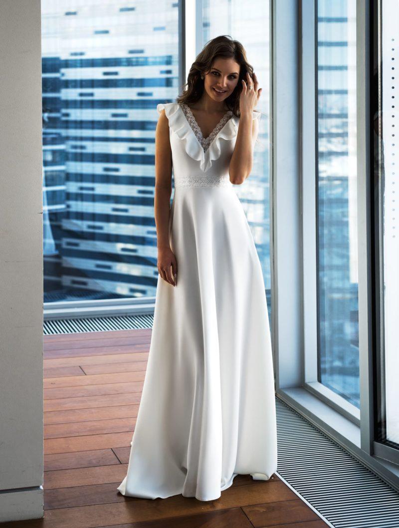 Атласное свадебное платье с вырезом, украшенным оборками.