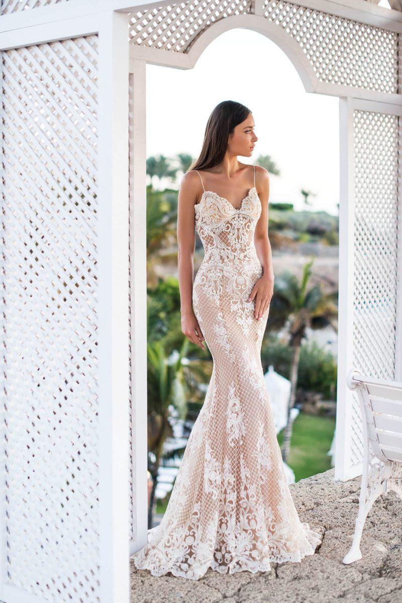Облегающее свадебное платье на бежевой подкладке под белым кружевом.