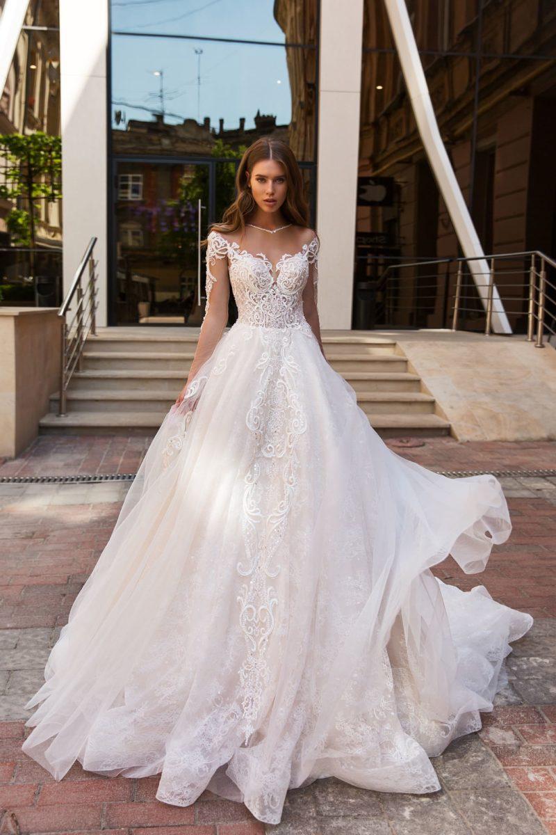 Многослойное свадебное платье с длинным рукавом и аппликациями.