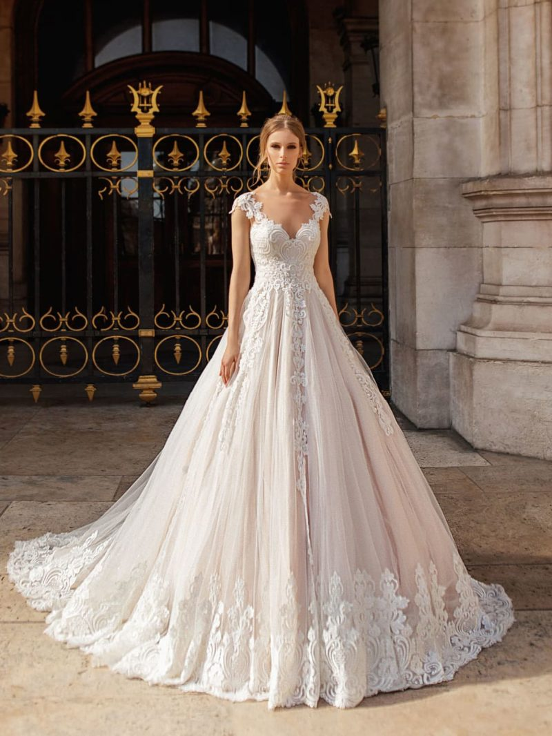 Пышное пудровое свадебное платье с белой кружевной отделкой.