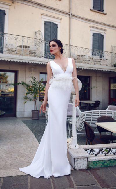 Облегающее свадебное платье с глубоким вырезом и поясом с перьями.