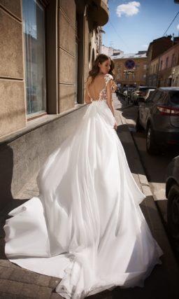 Свадебное платье с пышным шлейфом и вырезом на спине.