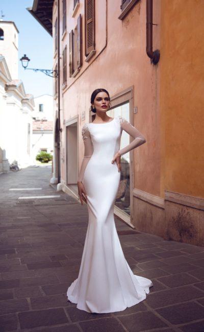 Закрытое атласное свадебное платье с полупрозрачным рукавом.