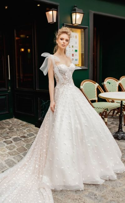 Свадебное платье с бантами на плечах и пышной юбкой.