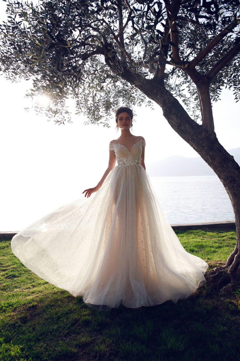 Бежевое свадебное платье с открытой спинкой и аппликациями.
