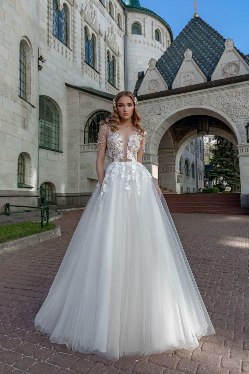 Пышное свадебное платье с глубоким вырезом и аппликациями.
