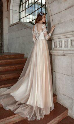 Свадебное платье с длинным рукавом и бежевой юбкой.