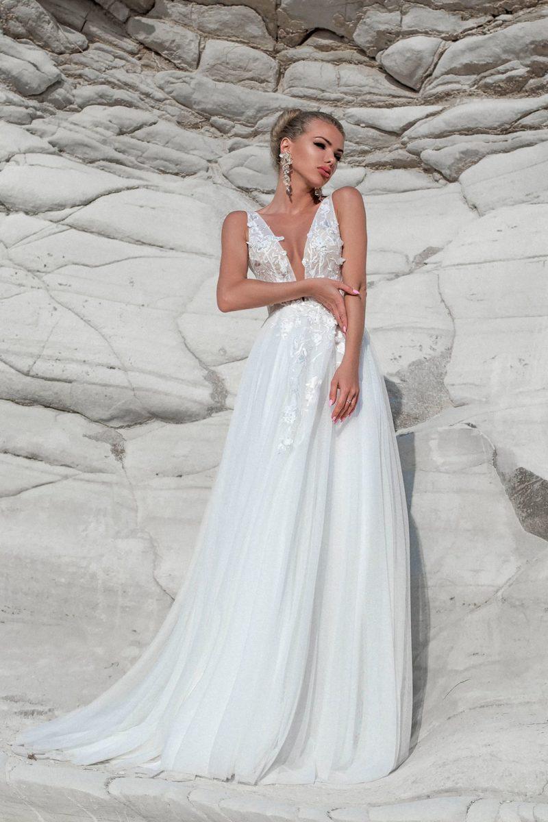 Свадебное платье с V-образным вырезом до талии и аппликациями.