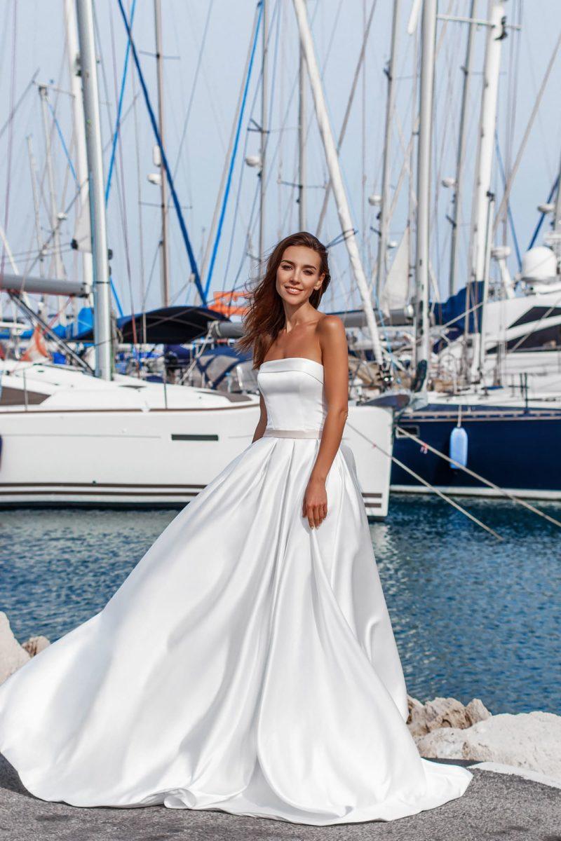 Атласное свадебное платье пышного кроя с открытым прямым лифом.
