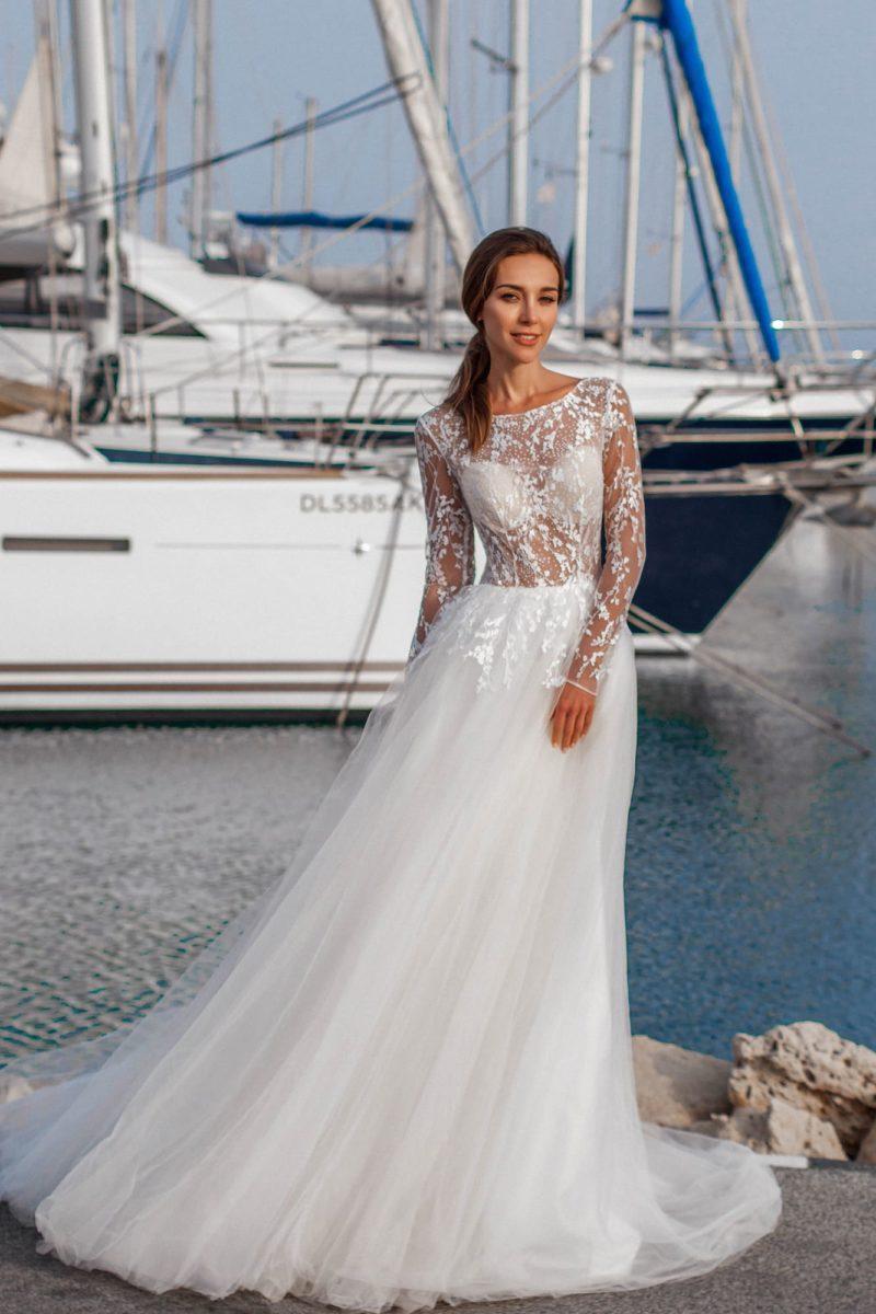 Пышное свадебное платье с длинным рукавом и объемным шлейфом.