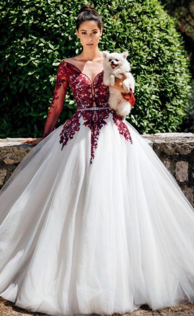 Свадебное платье пышного кроя с красной кружевной отделкой.