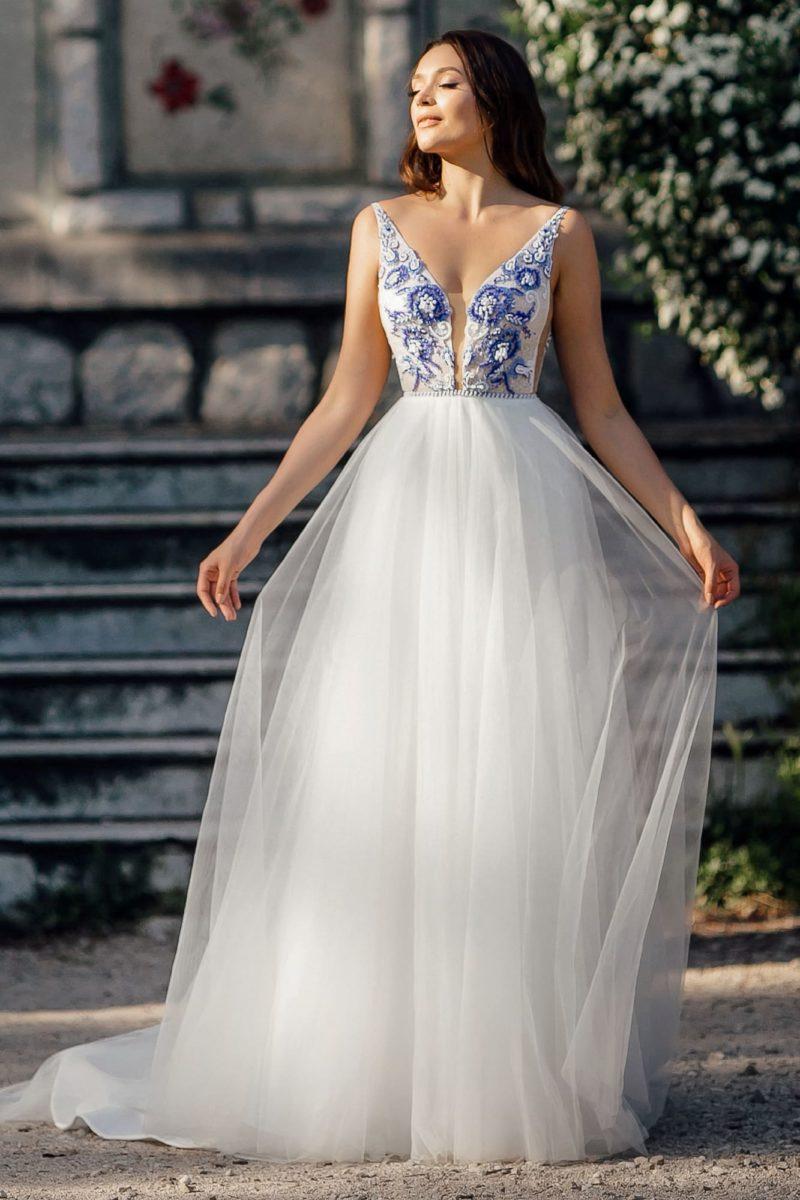 Свадебное платье с голубой отделкой лифа и многослойным низом.